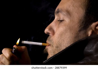 Young man in a leather jacket smoking a cigarette
