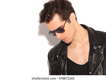 young man in leather jacket and sunglasses looks down on white studio background