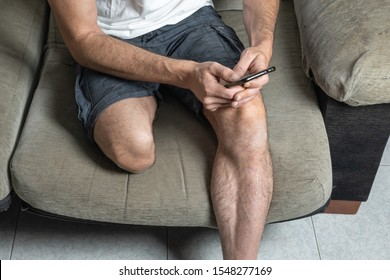 Young man with leg amputation sitting on sofa with mobile phone in hand