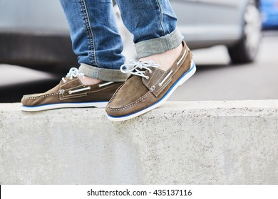 Young man legs and brown moccasins, urban fashion style in the city