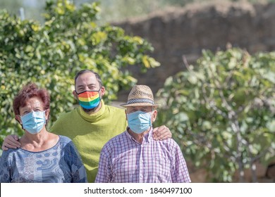 young man with lgtbi flag mask posing with his older parents with surgical face protection mask due to the global pandemic of the coronavirus, covid-19, concept of homosexuality and acceptance.