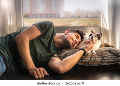 young man lies down next to black and white cat and caresses his head