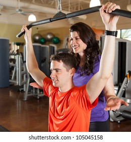 Young Man Lifting Weights with Personal Trainer