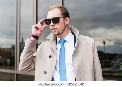 a young man in a light coat and sunglasses looking into the distance. Portrait of a businessman. man holding black glasses
