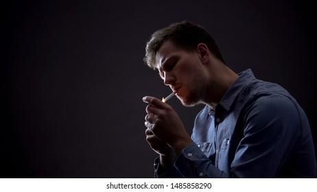 Young man lighting cigarette in dark room, unhealthy habit, harmful effect