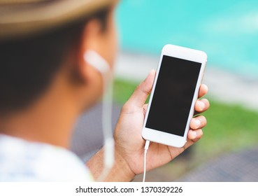 Young man listen music on smartphone while sitting near swimming pool. Relax concept.