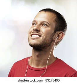 young man listen to music on a lights background