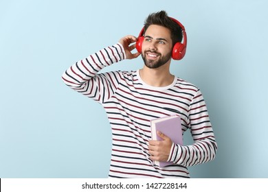 Young man listening to audiobook on light background