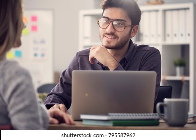 Young man listening a client in the office