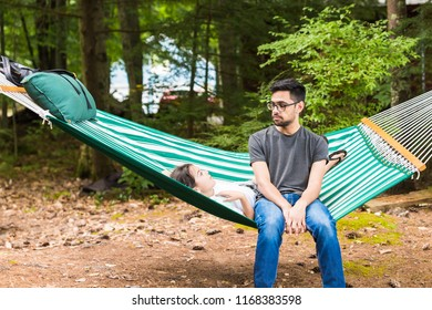 A young man is listening to hhis younger sister laying in a green hammock