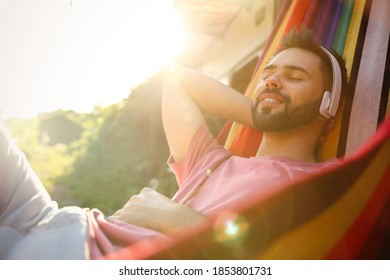 Young man listening to music in hammock near motorhome outdoors on sunny day