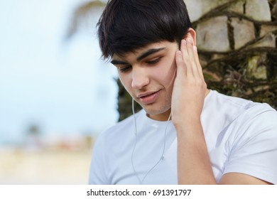 Young man listening music holding earphone