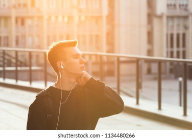 Young man listening to music, looking aside and enjoying nice evening time.