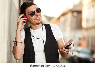 Young man listening to music on the street