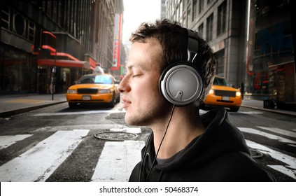 Young man listening to music on a city street