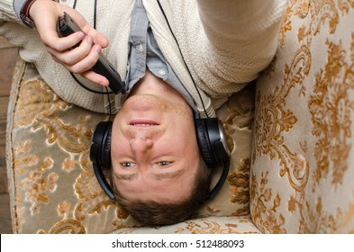 Young man is listening music on sofa with phone in the left hand