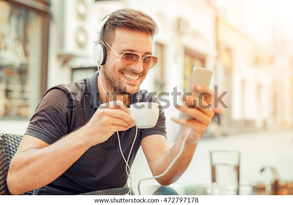 Young man listening to music on a smart phone in cafe