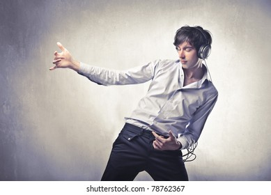Young man listening to music and playing an invisible guitar