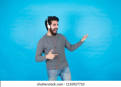 young man listening to music wearing his earphone and pretend that he plays guitar, standing on a blue background.