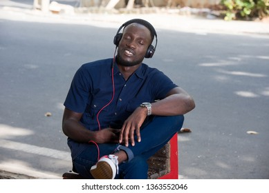 young man listens to music with headphones while sitting on a chair outside in the day. he listens to music with his eyes closed.