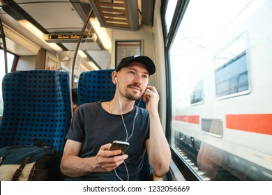 A young man listens to a music or podcast while traveling in a train.
