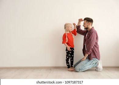 Young man and little girl measuring their height indoors