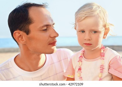 young man with little girl on beach