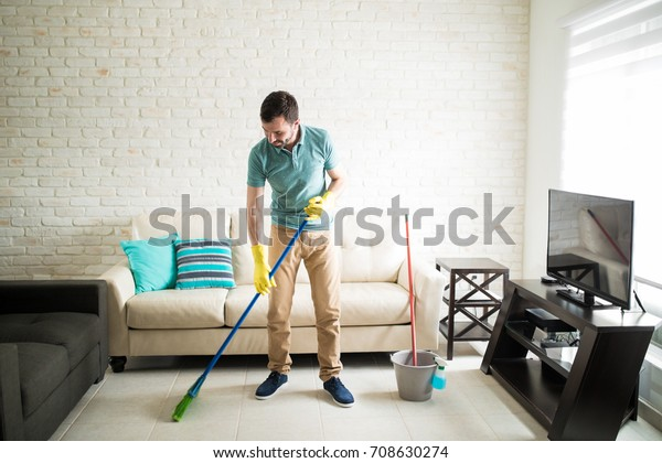 Young man living alone in his apartment sweeping the living room to keep it clean