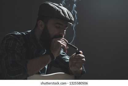 Young man with long beard in vintage style, posing in studio. Low light. Texture effect and film grain add. Not camera noise.