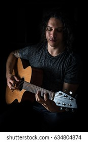 Young man with long curly hair playing an acoustic guitar.