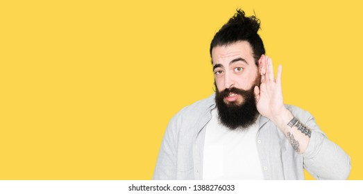 Young man with long hair, beard and earrings smiling with hand over ear listening an hearing to rumor or gossip. Deafness concept.