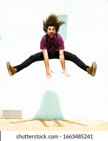 young man with long hair jumping very tall with open legs and smiling
