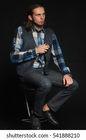 Young man with long hair sitting on a chair and smokes an electronic cigarette. A man sits on a black background.