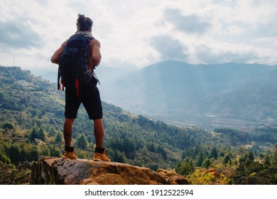Young man with long hair without shirt and big backpack on rock in mountain looking the city. Man standing in shorts and black backpack. Man bun.