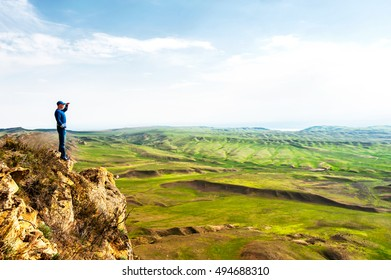 Young man look out to view at top of rock cliff on blue cloudy sky background. Summertime colorful horizontal image. Azerbaijan border, David Gareja, Georgia.