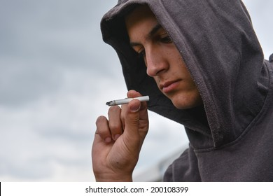 Young man looked at the cigarette and is undecided whether to smoke or not