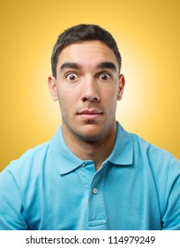 Young man looking amazed over light orange gradient