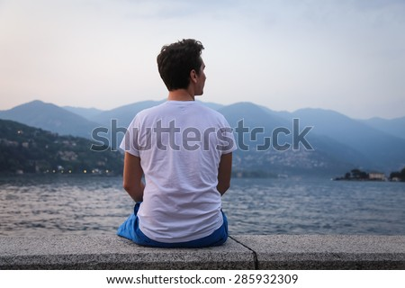 The young man looking at the beautiful view at the lake