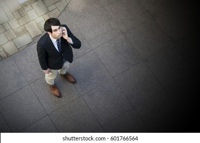 young man looking up and calling with smart phone