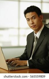 Young man looking at camera, using laptop