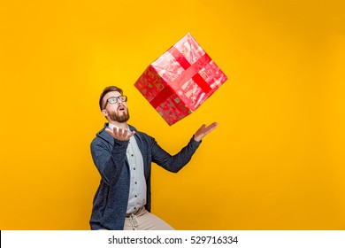 Young man looking casual in surprise throwing big red present gift box in air on orange studio background