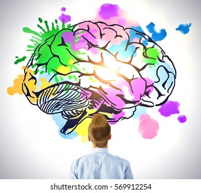 Young man looking at creative colorful brain sketch on light background. Brainstorming concept