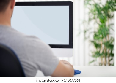 Young man looking at empty computer screen, back view