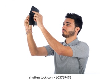 Young man looking to empty wallet, isolated