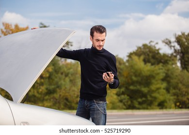 A young man looking for the evacuation of the service number, because his car broke down