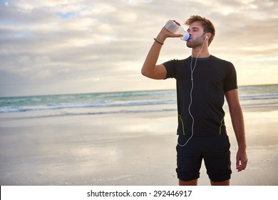 Young man looking fit and sporty drinking from his water bottle while enjoying a morning run on the beach