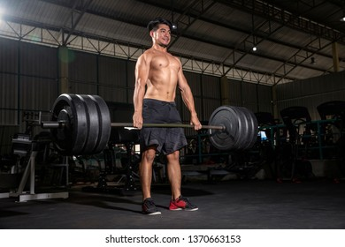 A Young man looking focused while lifting heavy weights barbell during a workout session in a dark gym - Image