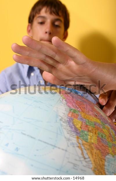 young man looking at globe