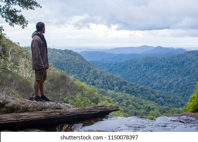 Young man is looking to the Goldcoast, from Springbrook National Park in Australia