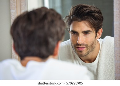 Young man looking himself in bathroom mirror